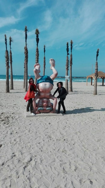 Tourists posing for a photo next to David Ben-Gurion statue in Tel Aviv beach.