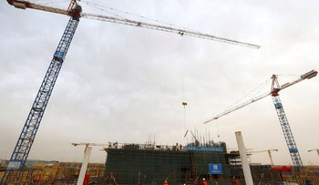Construction machines and labourers work at the site of the future Iconic Tower skyscraper, in the business district, being built by China State Construction Engineering Corp (CSCEC) in the New Administrative Capital (NAC) east of Cairo, Egypt May 2, 2019