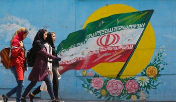 Girls walk in front of a mural showing the Iranian national flag in the centre of the  capital Tehran, on April 23, 2019