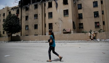 Palestinian girl walks by a house following a late night Israeli missile strike in town of Beit Lahiya, northern Gaza Strip, May 6, 2019.