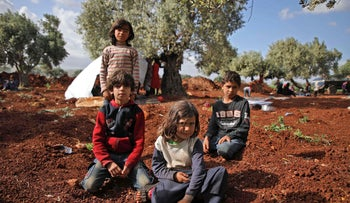 File photo: Displaced Syrian children sit in a field near a camp for displaced people in the village of Atme, in the jihadist-held northern Idlib province, May 8, 2019.