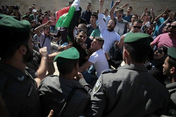 Palestinian men protest in front of Israeli border police officers as Israelis enter Jerusalem's Old City through Damascus Gate during a march celebrating Jerusalem Day, Sunday, May 17, 2015.