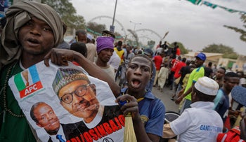 Supporters of Nigeria's President Muhammadu Buhari carry his poster as they march to celebrate his electoral win, on a street in Kano, Nigeria, February 27, 2019