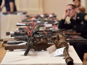 File photo: Police officers display captured weapons, March 2019.