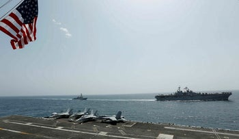 In this Friday, May 17, 2019, photo, released by the U.S. Navy, the amphibious assault ship USS Kearsarge, right, and the Arleigh Burke-class guided-missile destroyer USS Bainbridge, left, are seen from the Nimitz-class aircraft carrier USS Abraham Lincoln as they sail in the Arabian Sea