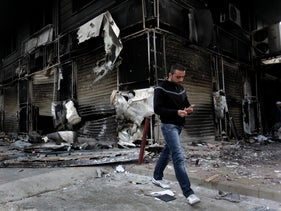 FILE Photo: A Syrian man  walks next to a burned shop which was destroyed during  violence between security forces and armed groups in  Latakia, northwest of Damascus, Syria.