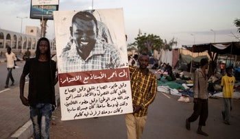 Protesters carry posters featuring photos of the martyrs as thousands marched toward the main sit-in outside the military headquarters in Khartoum, Sudan, Saturday, April 20, 2019.