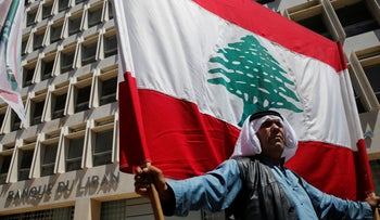 A retired Lebanese soldier holds a national flag, during a protest in front the central bank at cuts proposed in the 2019 draft austerity budget. Beirut, Lebanon, May 13, 2019