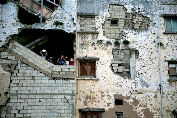 Syrian refugee children stand on the stairs of their apartment in a building damaged during Lebanon's 1975-1990 civil war on a former Beirut frontline, Lebanon. Nov. 28, 2015