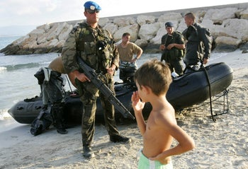 A Spanish soldier on secondment to UNIFIL holding a M60 machine gun stands guard near navy divers as Lebanese boy looks on. Rest House Hotel beach in the southern Lebanese city of Tyre. Sept. 14, 2006