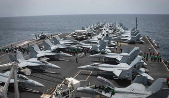 In this Sunday, May 19, 2019, photo released by the U.S. Navy, sailors partake in a foreign object and debris walk-down on the flight deck of the Nimitz-class aircraft carrier USS Abraham Lincoln in the Arabian Sea