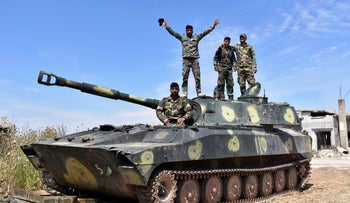 File photo: Syrian army soldiers flash the victory sign as they stand on their tank in the village of Kfar Nabuda, in the countryside of the Hama province, May 11, 2019.