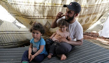 Ali, 25, a displaced Syrian farmer from the al-Ahmed family, holds his two daughters in an olive grove in the town of Atmeh, Idlib province, Syria, May 16, 2019.