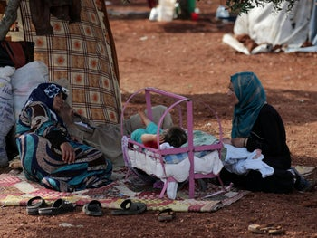 Two displaced Syrian women from the al-Ahmed family sit together in an olive grove in the town of Atmeh, Idlib province, Syria, May 16, 2019.