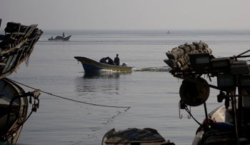Palestinian fishermen unload their catch from boats after a night fishing trip, in the Gaza Seaport, Tuesday, May 21, 2019.