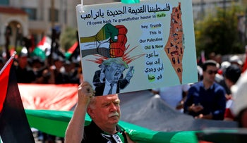 A Palestinian demonstrator holding an anti-U.S. slogan during a rally marking the 71st anniversary of the 'Nakba,' or catastrophe, in Ramallah on May 15, 2019.