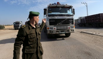 File photo: A member of the Palestinian Authority security forces waves forth a truck carrying goods at the Kerem Shalom border crossing in the southern Gaza Strip, November 7, 2017.