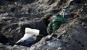 A soldier takes part in the exhumation of a mass grave containing the remains of about 730 prisoners of a former Jewish ghetto in the center of Brest, Belarus February 26, 2019.