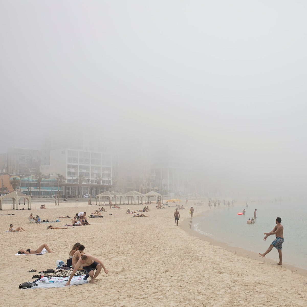 People enjoying the beach in Tel Aviv, under a heavy fog which stemmed from cold air that approached the coast and warmer air that entrapped it.