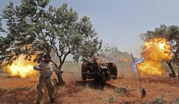 A Syrian fighter from the Turkish-backed National Liberation Front (NLF) fires a heavy artillery gun from the rebel-held Idlib in the northern part of Hama province, on May 22, 2019