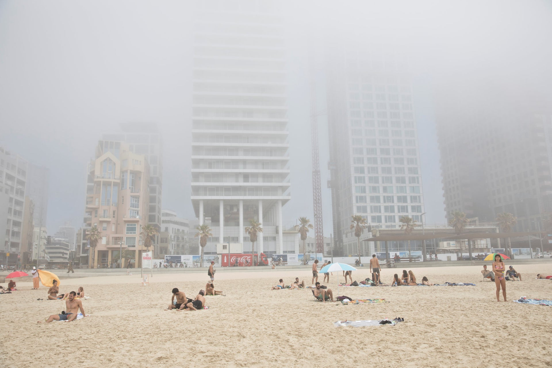 People at a beach in Tel Aviv, under the heavy dust.