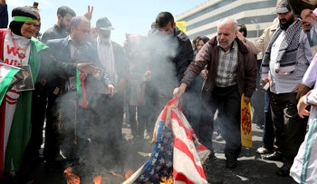 Iranian worshippers burn a representation of a U.S. flag during a rally after Friday prayer in Tehran, Iran, Friday, May 10, 2019.