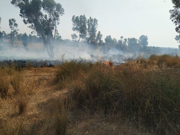 Flames seen in a field after an incendiary balloon launched from the Gaza Strip set it on fire in southern Israel, May 22, 2019