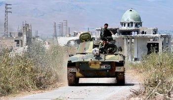 Syrian army forces enter the town of Kafr Nabuda, about 40 kilometers north of Hama, May 11, 2019.