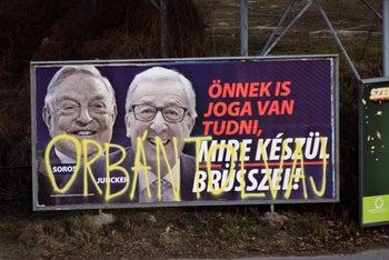 """A billboard from a campaign of the Hungarian government showing George Soros, left, and EU Commission President Jean-Claude Juncker with the caption """"You, too, have a right to know what Brussels is preparing to do,"""" Budapest, February 26, 2019. The words """"Orban thief"""" are graffitied on the poster."""