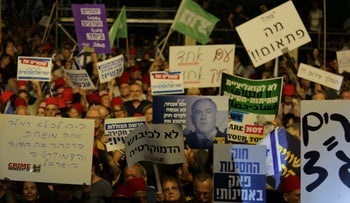 Protesters hold up signs in Tel Aviv on May 25, 2019.
