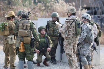 A group of airsoft players, including Sigcchi (crouching) getting their orders during a game.