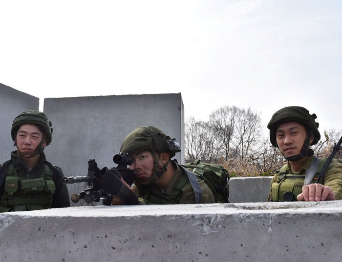 Sigcchi, right, standing next to two teammates during a game of airsoft.