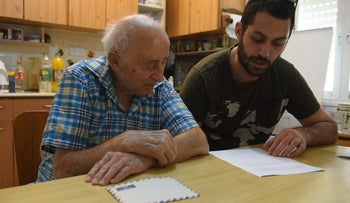 Ephraim Golan, left, listening to extracts from Judit Ornstein's diary being read to him by Nir Itzik from the Moreshet Archive, where the journal is stored.