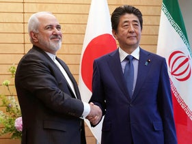 Iranian Foreign Minister Mohammad Javad Zarif, left, and Japanese Prime Minister Shinzo Abe, right, shake hands at Abe's official residence in Tokyo Thursday, May 16, 2019. (