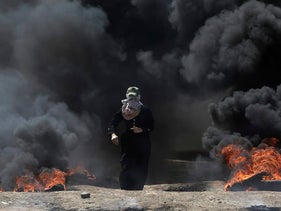 A Palestinian woman walks through black smoke from burning tires during a protest on the Gaza Strip's border with Israel, Monday, May 14, 2018.
