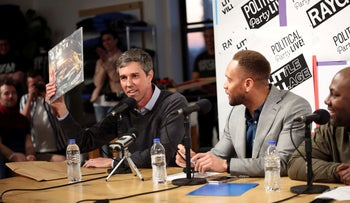 """Democratic 2020 presidential candidate Beto O'Rourke presents a vinyl record gift to """"Political Party Live"""" podcast hosts in Cedar Rapids, Iowa, U.S., March 15, 2019."""