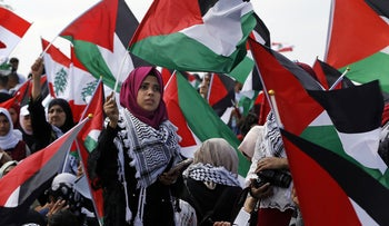 """Palestinians living in Lebanon hold flags during a rally to mark the 70th anniversary of the """"nakba,"""" or """"catastrophe"""" of 1948, at the Beaufort Castle near the Israeli border, Tuesday, May 15, 2018."""
