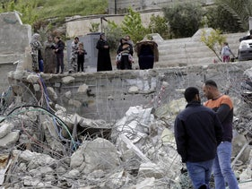 Palestinians watch a family house destroyed by Israeli authorities in east Jerusalem's neighborhood of Silwan, Wednesday, April 17, 2019
