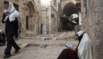 File photo: A Palestinian woman reads a copy of the Kuran as a Jewish Orthodox man walks past her in Jerusalem's Old City on September 10, 2015.