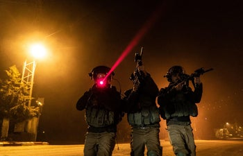 Israeli soldiers patrolling with the help of laser technology.