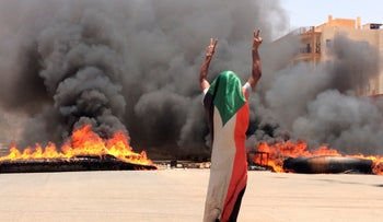 A protester wearing a Sudanese flag flashes the victory sign in front of burning tires and debris on road 60, near Khartoum's army headquarters, in Khartoum, Sudan, Monday, June 3, 2019.