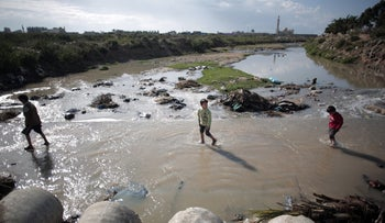FILE Photo: Children cross through sewage water in Mighraqa neighborhood on the outskirts of Gaza City, April 13, 2016.