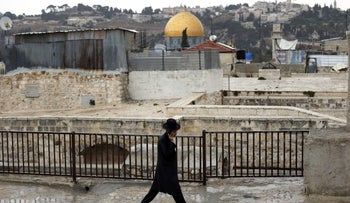 FILE Photo: An ultra-Orthodox man walks on a roof in the Old City with the Dome of the Rock seen in the background.
