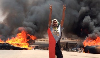 A protester flashes the victory sign in front of burning tires and debris on road 60, near army headquarters, in Khartoum, Sudan, June 3, 2019.