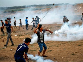 A Palestinian hurls stones at Israeli forces amidst clashes during a protest by the border with Israel marking al-Quds Day in the central Gaza Strip, May 31, 2019.