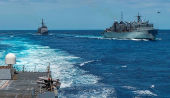 U.S. Navy Ticonderoga-class cruiser USS Leyte Gulf (CG 55) pulling alongside (R) the fast combat support ship USNS Arctic (T-AOE 9) after the Arleigh Burke-class guided-missile destroyer USS Bainbridge (DDG 96) completes its replenishment-at-sea in the Mediterranean, May 8, 2019.