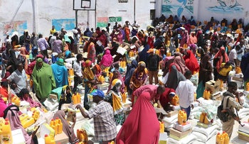 Internally displaced people (IDP) gather in the Shingani District of the Somali capital Mogadidshu to collect food rations being distributed to the families on May 15, 2019