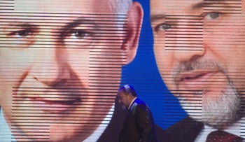 Then-Foreign Minister Avigdor Lieberman walking under a screen showing him and Prime Minister Benjamin Netanyahu during the inauguration of their election campaign in Jerusalem, December 25, 2012.