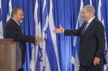 Avigdor Lieberman and Benjamin Netanyahu shaking hands after announcing an electoral pact ahead of the 2013 Knesset election, October 2012.