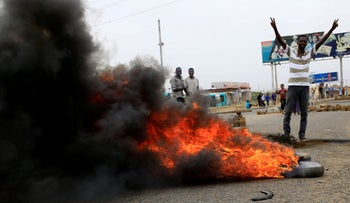 A Sudanese protester gestures near burning tires in Khartoum, Sudan, June 4, 2019.